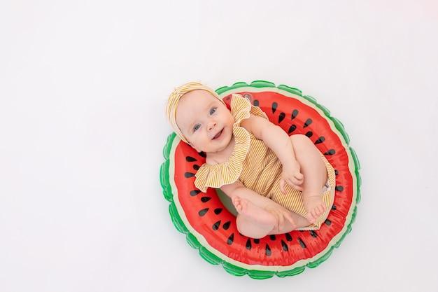 Uśmiechnięte Dziecko W Kostiumie Kąpielowym Z Kółeczkiem W Kształcie Arbuza Leży. Premium Zdjęcia