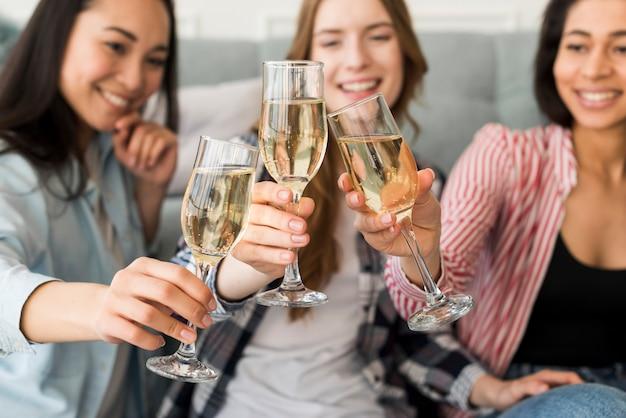 Uśmiechnięte i siedzące dziewczyny trzymające szklanki i brzęczące razem Darmowe Zdjęcia