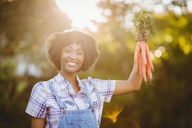 Uśmiechnięte Kobiety Mienia Marchewki W Ogródzie Premium Zdjęcia