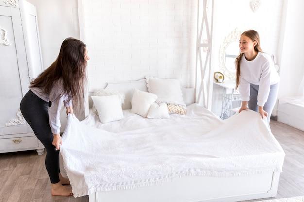 Uśmiechnięte Kobiety Robią łóżko Darmowe Zdjęcia
