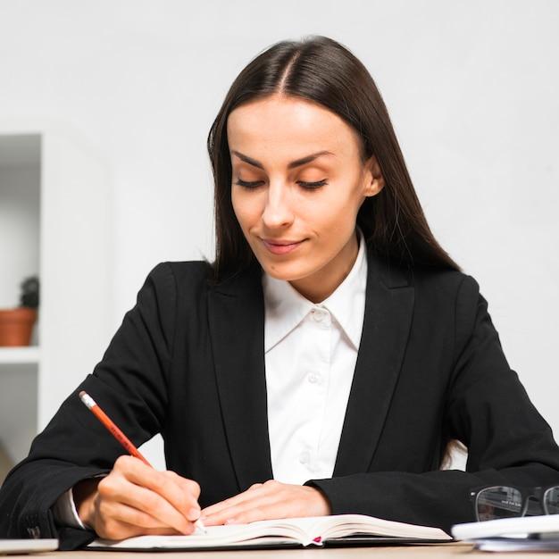 Uśmiechnięte młode bizneswomanu writing notatki dzienniczek z ołówkiem Darmowe Zdjęcia