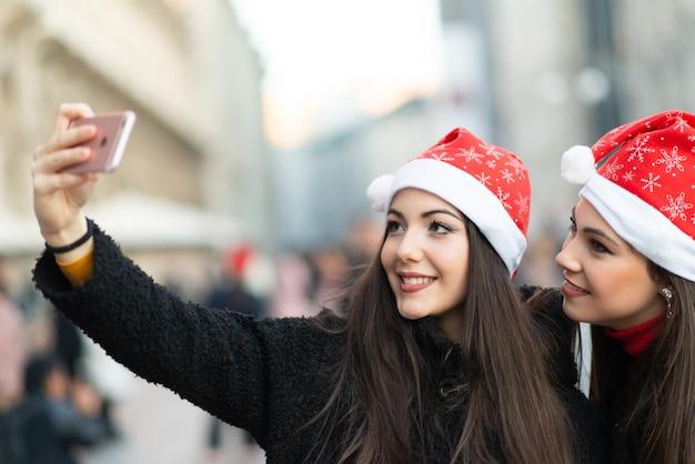 Uśmiechnięte Młode Kobiety W Bożenarodzeniowym Kapeluszu Bierze Zdjęcie Wpólnie Premium Zdjęcia