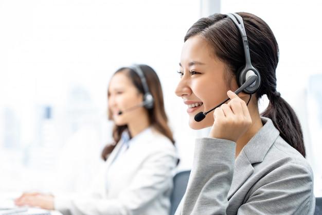 Uśmiechniętego Telemarketingu Azjatycka Kobieta Pracuje W Centrum Telefonicznego Biurze Premium Zdjęcia