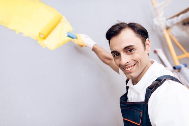 Uśmiechnięty arab mistrz z farbą i muśnięciem w ręce. Premium Zdjęcia