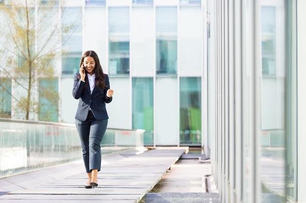 Uśmiechnięty Azjatycki Bizneswoman Opowiada Na Smartphone Darmowe Zdjęcia