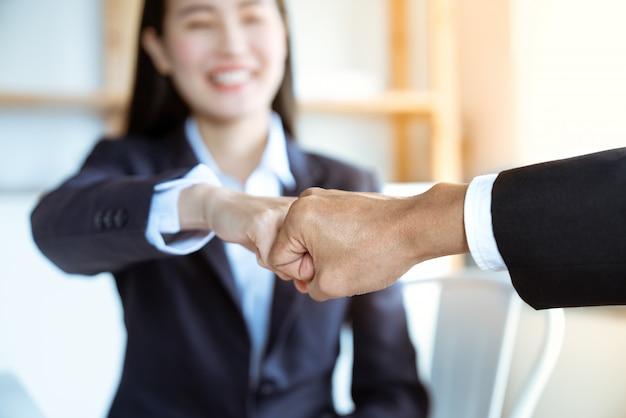 Uśmiechnięty azjatycki młody bizneswoman wpadać na siebie pięści z jej szefem po praca sukcesu wpólnie przy biurem pracy zespołowej pomyślny pojęcie Premium Zdjęcia