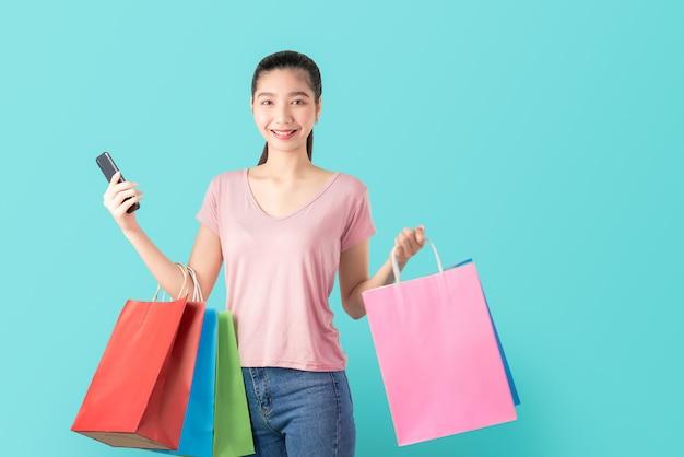 Uśmiechnięty azjatykci kobieta przypadkowego stylu mienia smartphone i torba na zakupy. Premium Zdjęcia