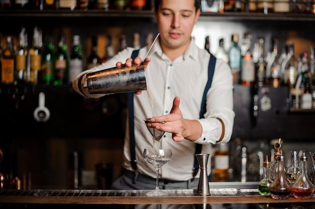Uśmiechnięty barman potrząsa fantazyjnym koktajlem Premium Zdjęcia