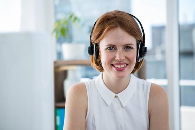 Uśmiechnięty biznes hipster siedzi przy biurku w słuchawkach Premium Zdjęcia