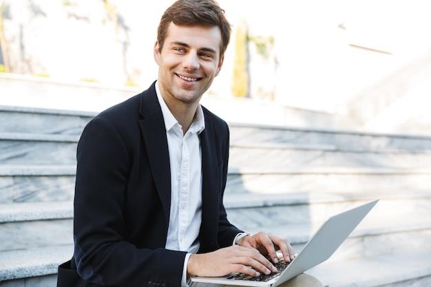 Uśmiechnięty Biznesmen Pracuje Na Komputerze Przenośnym Na Zewnątrz Premium Zdjęcia