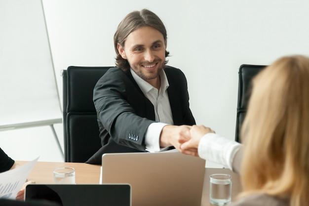 Uśmiechnięty biznesmen w kostiumu handshaking żeńskim partnerze przy grupowym spotkaniem Darmowe Zdjęcia