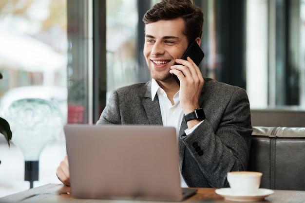 Uśmiechnięty Biznesmena Obsiadanie Stołem W Kawiarni Z Laptopem Podczas Gdy Opowiadający Smartphone Darmowe Zdjęcia