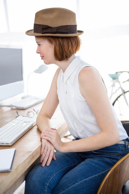 Uśmiechnięty bizneswomanu obsiadanie przy biurku patrzeje komputer Premium Zdjęcia