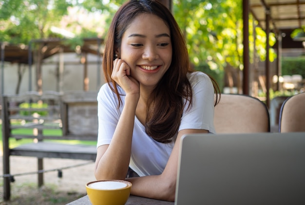 Uśmiechnięty Blogger Z Azji Siedzi W Kawiarni I Ogląda Kamerę Nagrywającą Wideo Na żywo Na Komputerze Osobistym. Widok Wideokonferencji Z Kamerą Internetową Z Przeglądarkami Online. Twórca Strony Internetowej I Recenzja Produktu Premium Zdjęcia