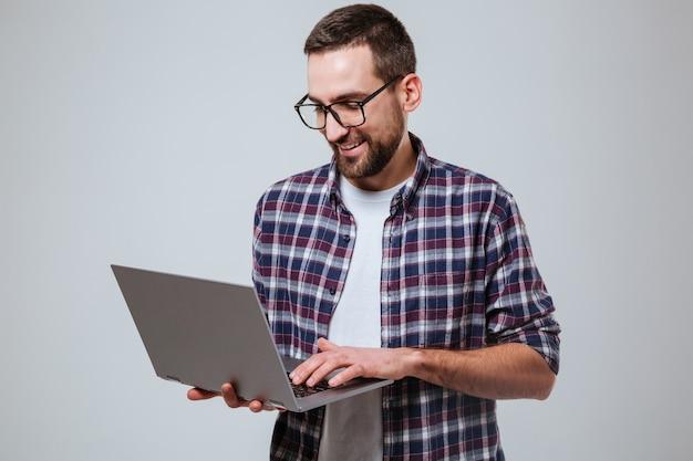 Uśmiechnięty Brodaty Mężczyzna W Eyeglases Używać Laptop Darmowe Zdjęcia