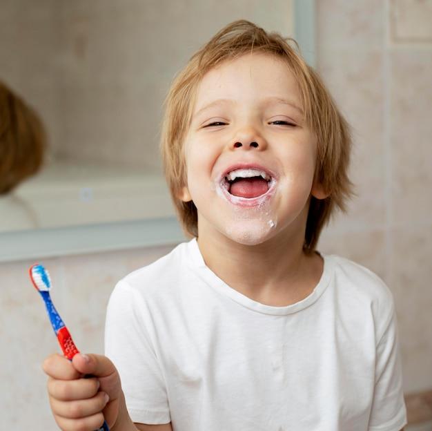 Uśmiechnięty Chłopiec Szczotkuje Zęby Premium Zdjęcia