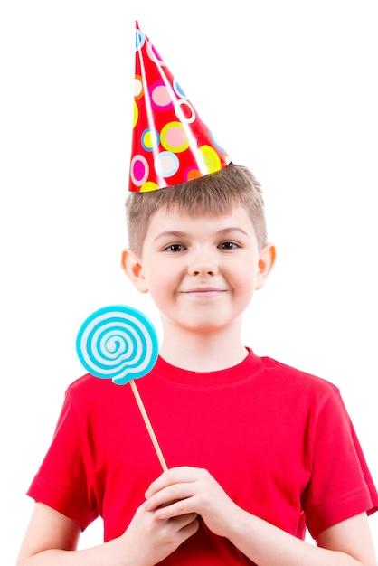Uśmiechnięty Chłopiec W Czerwonej Koszulce I Kapeluszu Strony, Trzymając Kolorowe Cukierki - Na Białym Tle. Darmowe Zdjęcia