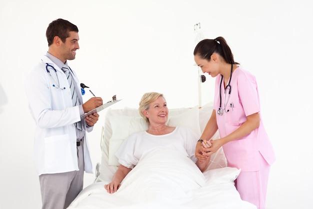 Uśmiechnięty Cierpliwy Lying On The Beach Między życzliwą Pielęgniarką I Lekarką Premium Zdjęcia