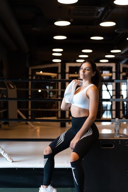 Uśmiechnięty Dysponowany Dziewczyny Mienia Ręcznik I Brać Odpoczynek W Gym. Darmowe Zdjęcia