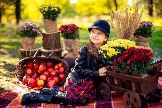 Uśmiechnięty dziecko siedzi w jesień parku z koszem czerwoni jabłka Premium Zdjęcia