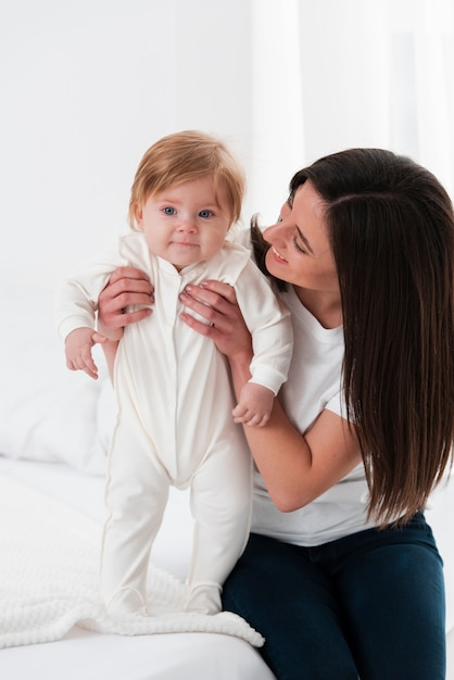 Uśmiechnięty dziecko trzymający matką i pozować Darmowe Zdjęcia