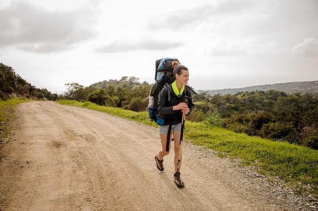 Uśmiechnięty Dziewczyny Odprowadzenie Na Zielonej ścieżce Z Wycieczkować Plecaka Premium Zdjęcia