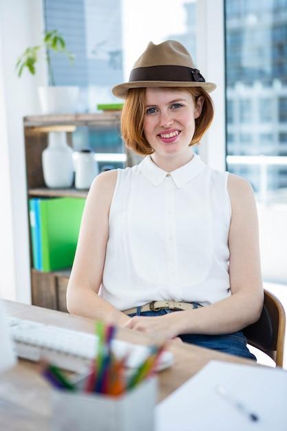 Uśmiechnięty hipster biznes kobieta siedzi przy biurku, ubrany w trylby Premium Zdjęcia