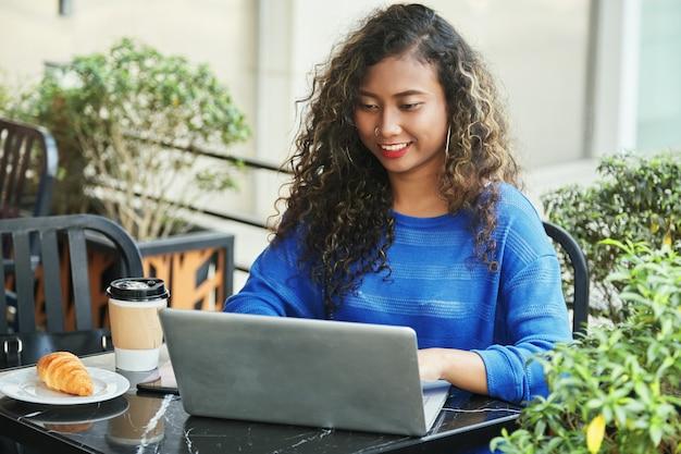 Uśmiechnięty Indonezyjski Bizneswoman Wyszukuje Laptop W Kawiarni Darmowe Zdjęcia