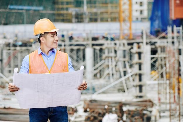 Uśmiechnięty Inżynier Budownictwa Lądowego, Odwracając Wzrok Premium Zdjęcia