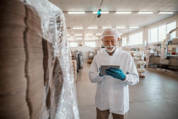 Uśmiechnięty Kaukaski Starszy Inspektor Dorosły Ubrany W Biały Mundur Za Pomocą Tabletu Do Oceny Jakości żywności W Zakładzie Spożywczym. Premium Zdjęcia