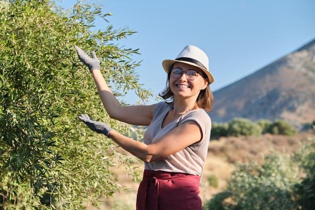 Uśmiechnięty Kobieta Właściciel Oliwny Ogród Wskazuje Drzewo Premium Zdjęcia