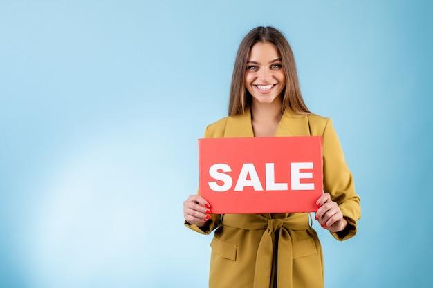 Uśmiechnięty kobiety mienia kopii przestrzeni sprzedaży czerwony znak odizolowywający nad błękitem Premium Zdjęcia