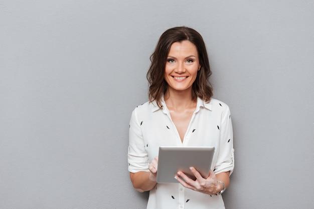 Uśmiechnięty Kobiety Mienia Pastylki Komputer W Rękach I Patrzeć Kamerę Na Szarość Darmowe Zdjęcia
