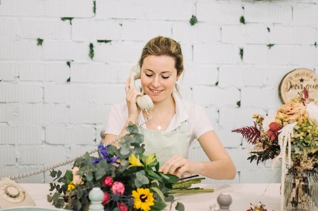 Uśmiechnięty Kwiaciarni Mówienie Na Telefonie Darmowe Zdjęcia
