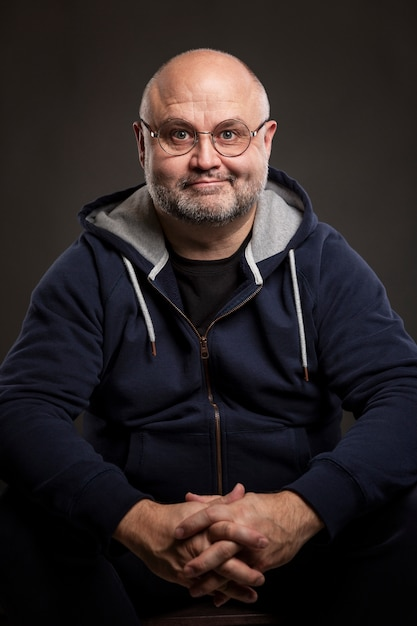 Uśmiechnięty łysy mężczyzna w okularach siedzi. czarny . pionowy. Premium Zdjęcia