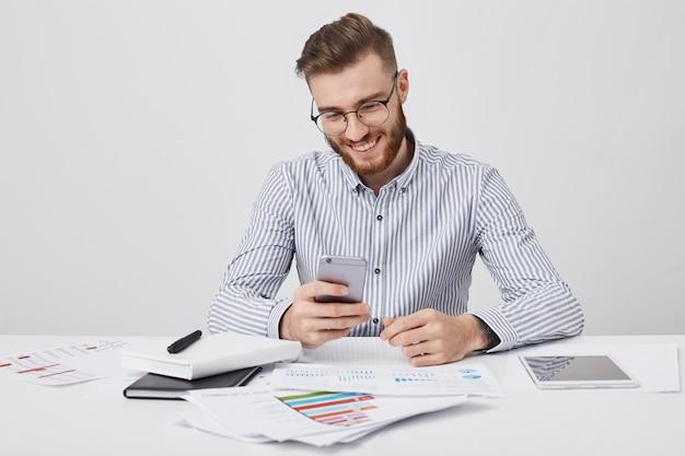 Uśmiechnięty Menadżer, Otoczony Licznymi Papierami I Gadżetami, Otrzymuje Gratulacje Na Telefon Komórkowy Od Przyjaciela, Podobnie Jak Urodziny Darmowe Zdjęcia