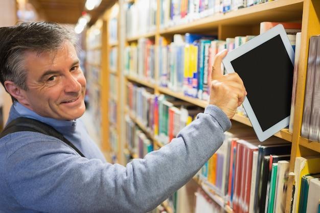 Uśmiechnięty Mężczyzna Bierze Pastylka Komputer Osobistego Od Półek Premium Zdjęcia