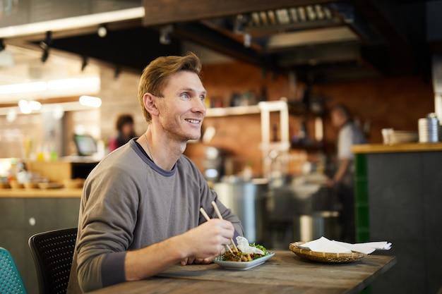 Uśmiechnięty Mężczyzna Cieszy Się Azjatyckiego Jedzenie Premium Zdjęcia