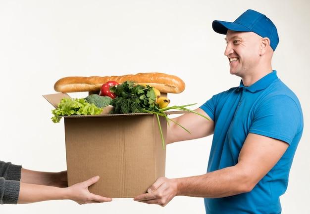 Uśmiechnięty Mężczyzna Dostarcza Karton Z Jedzeniem Darmowe Zdjęcia