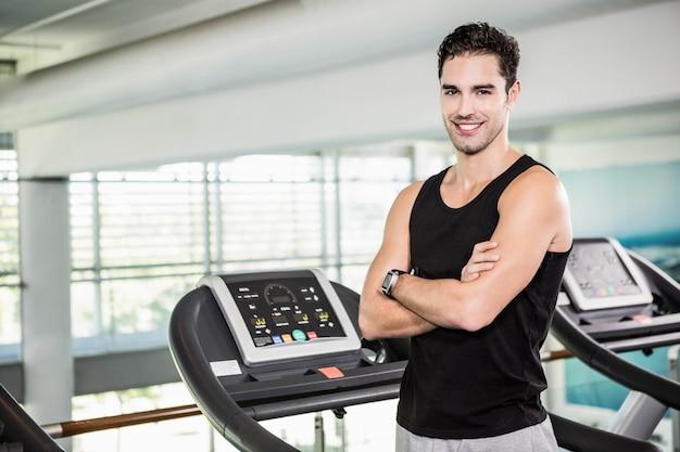 Uśmiechnięty mężczyzna na bieżni stojącej z rękami skrzyżowanymi na siłowni Premium Zdjęcia