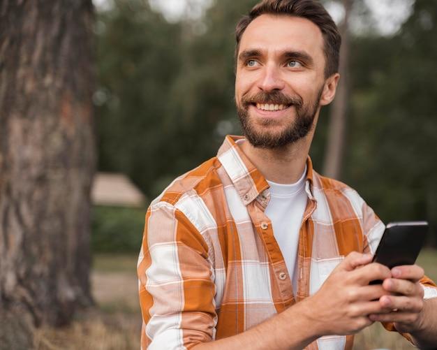 Uśmiechnięty Mężczyzna Na Zewnątrz Trzymając Smartfon Darmowe Zdjęcia