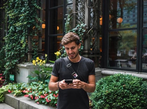 Uśmiechnięty Mężczyzna Na Zewnątrz Za Pomocą Smartfona Premium Zdjęcia