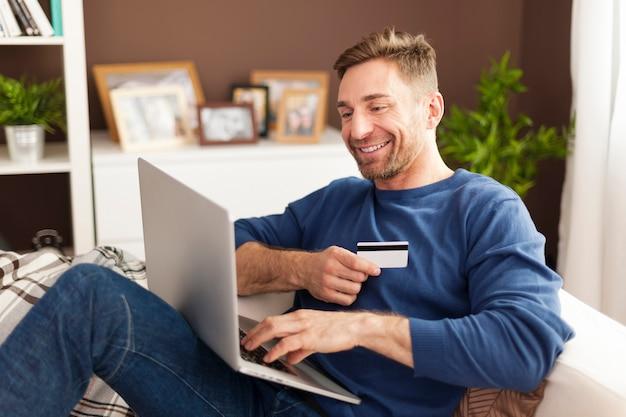 Uśmiechnięty Mężczyzna Podczas Zakupów Online W Domu Darmowe Zdjęcia