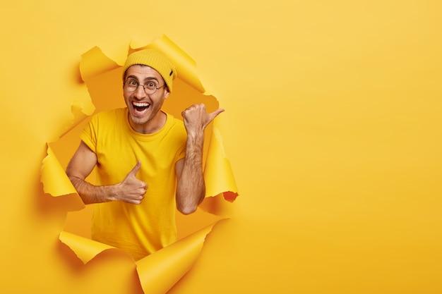 Uśmiechnięty Mężczyzna Pozuje Przez Podarty Papier Darmowe Zdjęcia