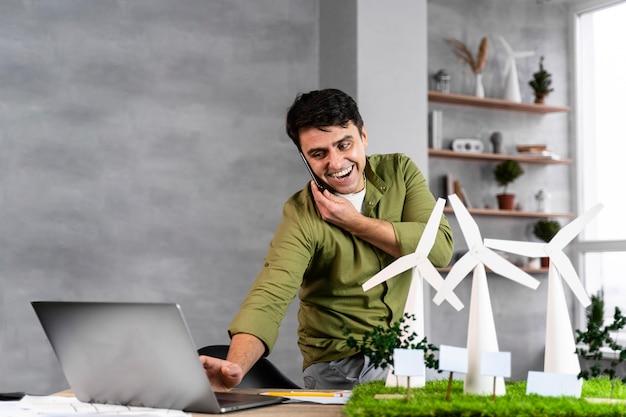 Uśmiechnięty Mężczyzna Pracujący Nad Projektem Ekologicznej Energii Wiatrowej, Rozmawiając Przez Telefon I Za Pomocą Laptopa Darmowe Zdjęcia