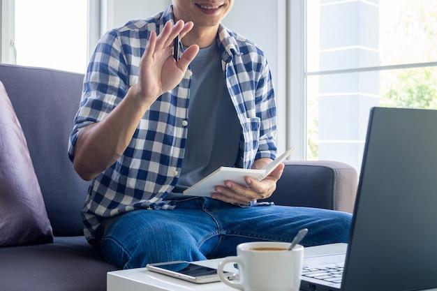 Uśmiechnięty Mężczyzna Pracuje Na Laptopie I Rozmawia Z Zespołem Za Pomocą Wideokonferencji Z Domu, Siedząc Na Kanapie. Premium Zdjęcia