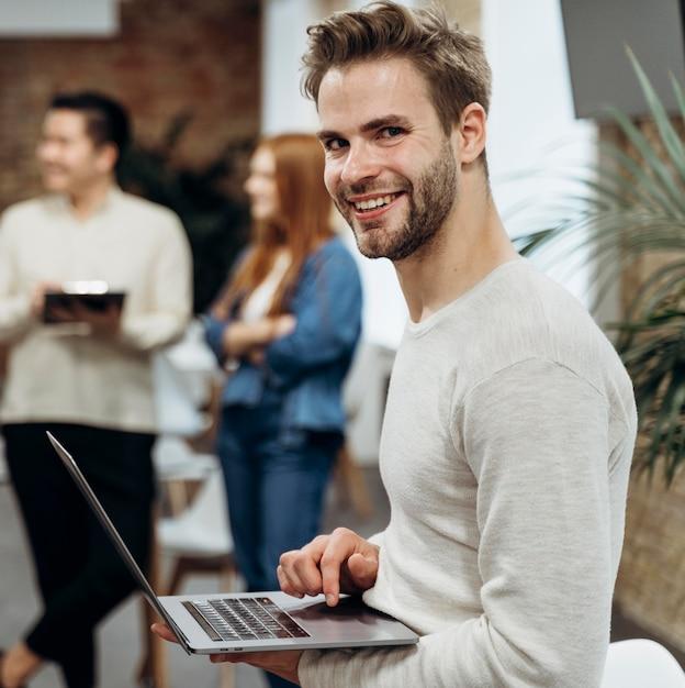Uśmiechnięty Mężczyzna Pracuje Na Laptopie Stojąc Darmowe Zdjęcia