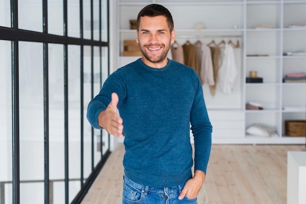 Uśmiechnięty mężczyzna ręką w kierunku kamery, aby uścisnąć dłoń Darmowe Zdjęcia