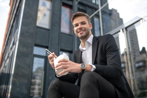 Uśmiechnięty Mężczyzna Siedzi Na Schodach I Je Azjatyckie Jedzenie Premium Zdjęcia