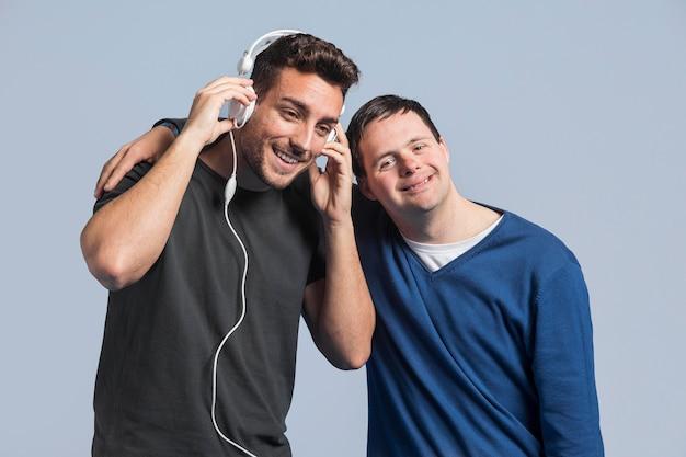 Uśmiechnięty Mężczyzna Słuchanie Muzyki Obok Przyjaciela Darmowe Zdjęcia